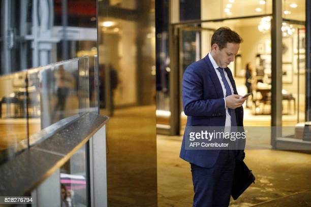 A businessman uses a smartphone as he stands in side a shopping centre near St Paul's Cathedral in central London on August 9 2017 World stock...