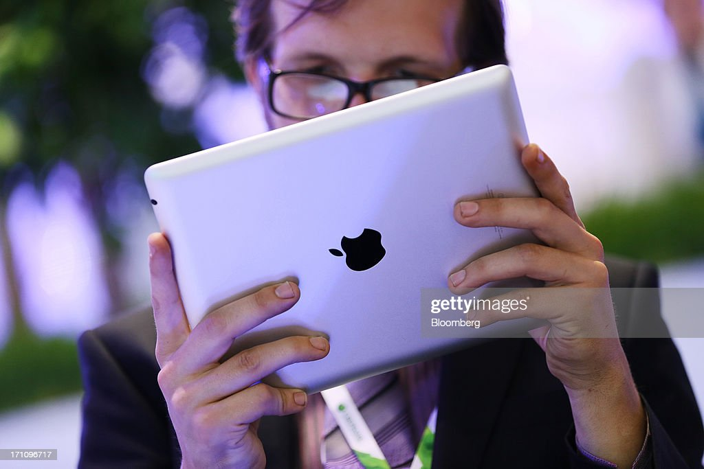A businessman uses an Apple Inc. iPad tablet on the closing day of the St. Petersburg International Economic Forum (SPIEF) in St. Petersburg, Russia, on Saturday, June 22, 2013. President Vladimir Putin unveiled a plan to jolt Russia's economy out of the worst growth in four years, promising to help the central bank cut inflation and pledging about $14 billion of savings to revamp roads and railways. Photographer: Andrey Rudakov/Bloomberg via Getty Images