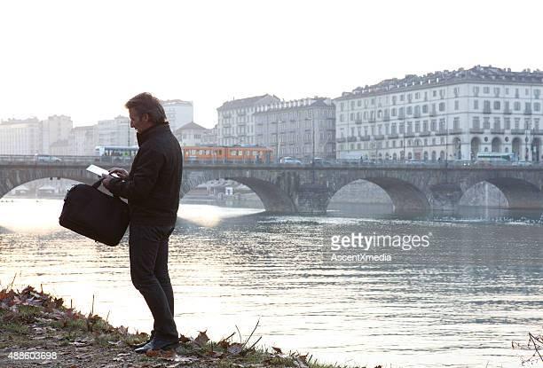 Businessman uses digital tablet above river