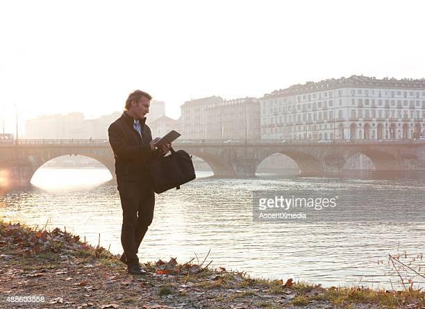 Businessman uses digital tablet beside river, sunrise