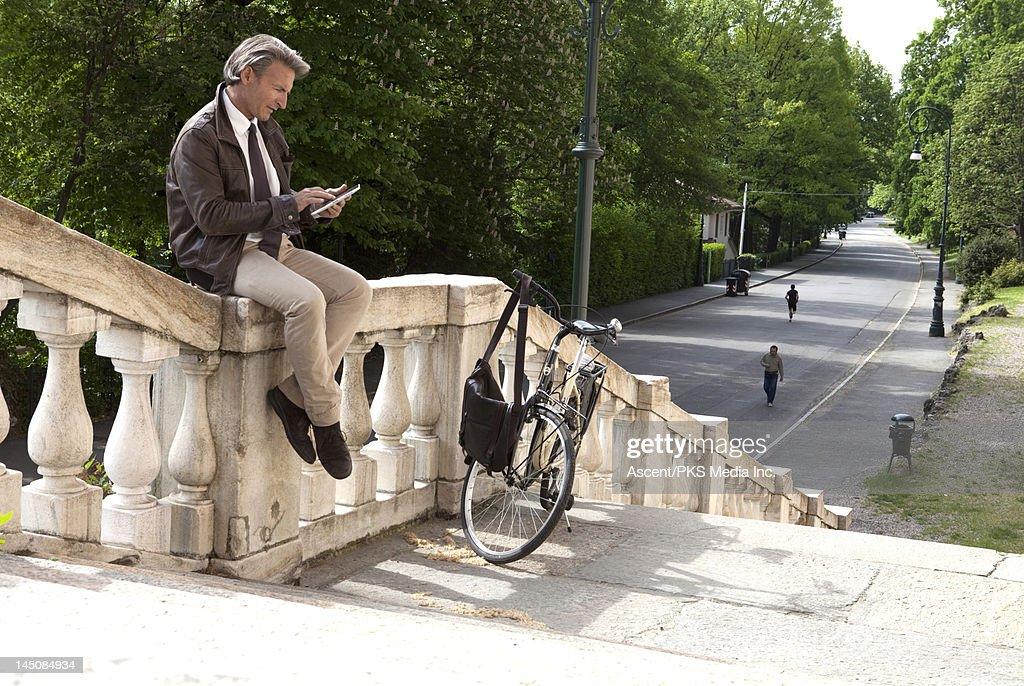 Businessman uses digital tablet on marble railing : Stock Photo