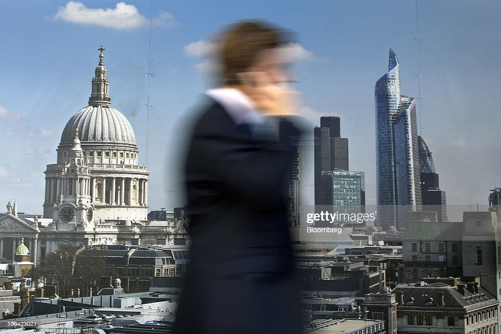 A businessman uses his mobile phone as he passes a poster depicting St. Paul's Cathedral, left, and the City, in London, U.K., on Friday, Aug. 17, 2012. Banks, insurers and other financial-services firms may eliminate a total of about 3,000 jobs across greater London as companies in the New York region add 9,000, according to U.K.-based researcher Oxford Economics Ltd. Photographer: Simon Dawson/Bloomberg via Getty Images