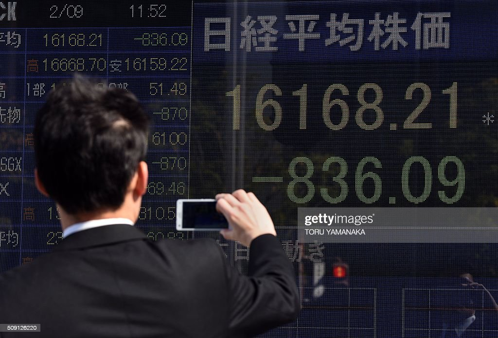 A businessman uses his smartphone to take pictures of an electric quotation board flashing the Nikkei key index of the Tokyo Stock Exchange (TSE) in front of a securities company in Tokyo on February 9, 2016. Tokyo shares tumbled nearly five percent, extending a global sell-off as a stronger yen dented exporters and after oil prices tanked again on fears of a deepening economic slowdown. AFP PHOTO/Toru YAMANAKA / AFP / TORU YAMANAKA