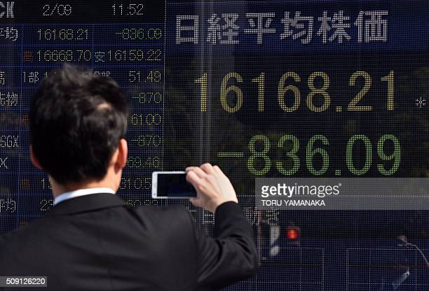 A businessman uses his smartphone to take pictures of an electric quotation board flashing the Nikkei key index of the Tokyo Stock Exchange in front...