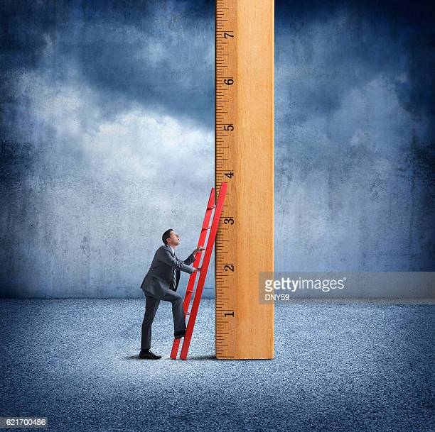 Businessman Uses Ladder To Climb Wooden Ruler