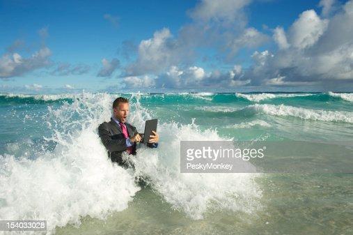 Uomo d'affari utilizzando Computer Tablet in quale si infrangono le grandi onde del mare : Stock Photo