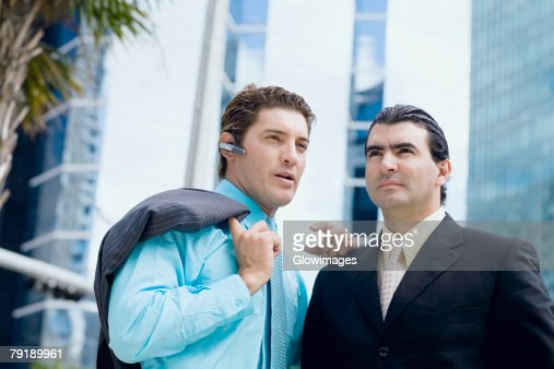 Businessman using a bluetooth device and another businessman standing in front of him : Stock Photo