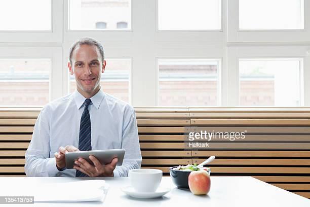 Un uomo d'affari utilizzando una tavoletta digitale per la sua pausa pranzo