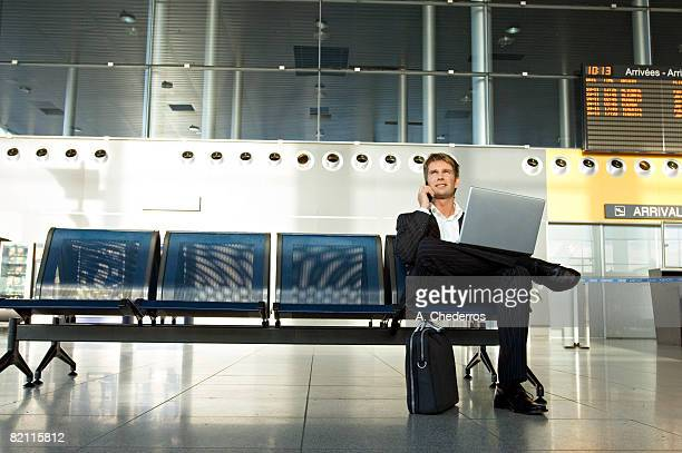 Businessman using a laptop and talking on a mobile phone