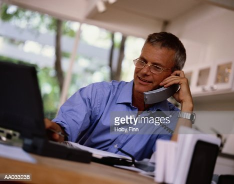 Businessman Using a Laptop and Talking on a Phone : Bildbanksbilder