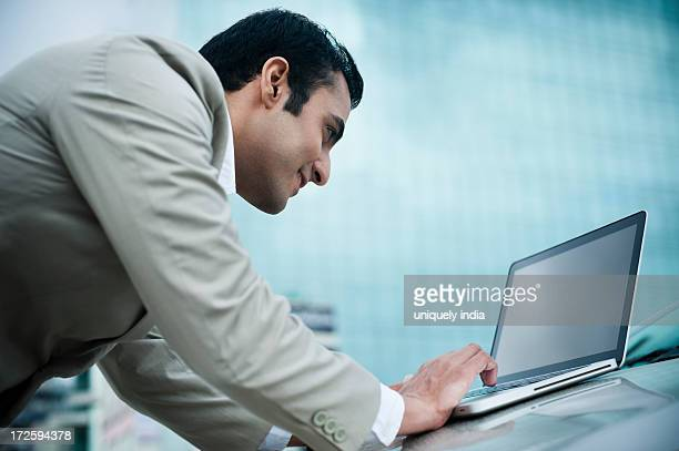 Businessman using a laptop on car bonnet and smiling