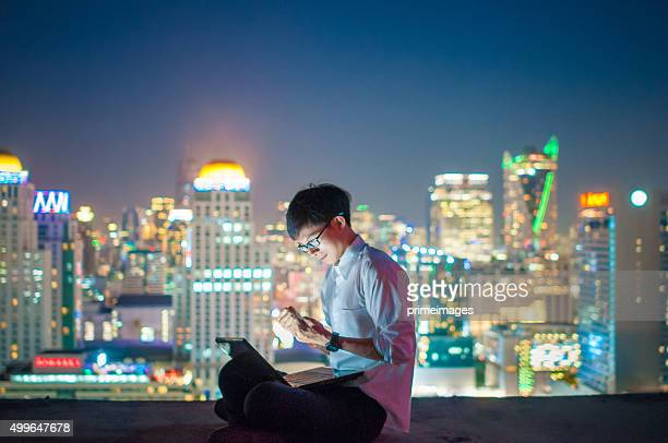Businessman using a laptop on the rooftop of a skyscraper