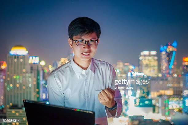 Geschäftsmann mit einem laptop auf dem Dach des Wolkenkratzer