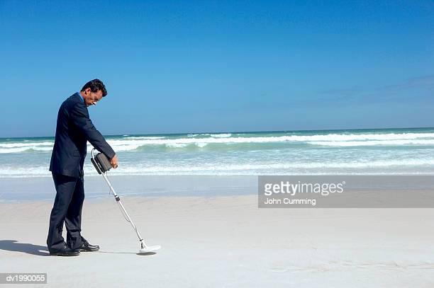 Businessman Using a Metal Detector on a Beach