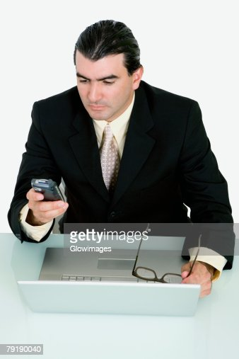 Businessman using a mobile phone in front of a laptop : Foto de stock