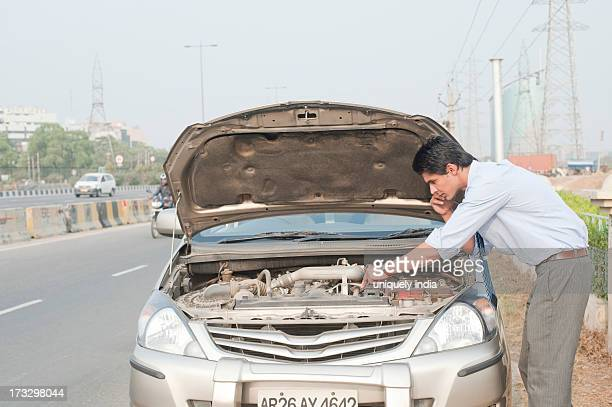 Businessman using a mobile phone near a broken down car, Gurgaon, Haryana, India