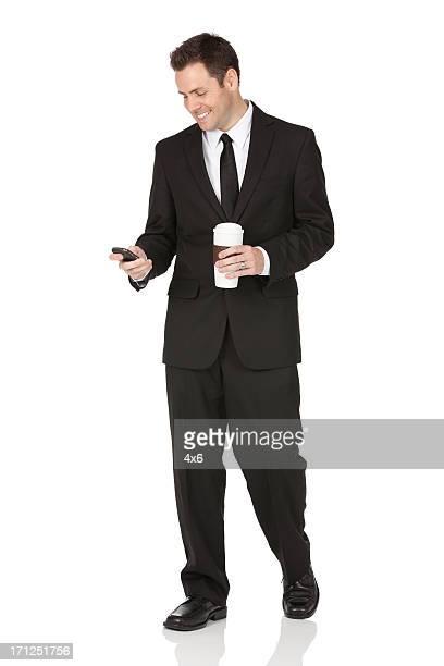 ビジネスマンが携帯電話を使用して、コーヒーを飲みながら