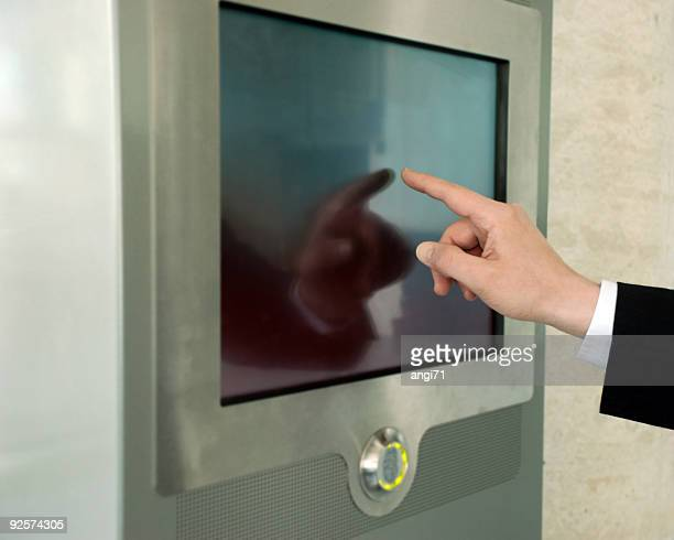 Businessman using a touch screen in office building wall