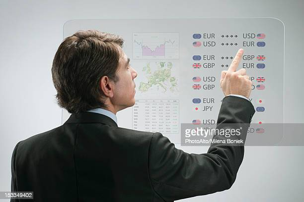 Businessman using advanced touch screen technology to view business data