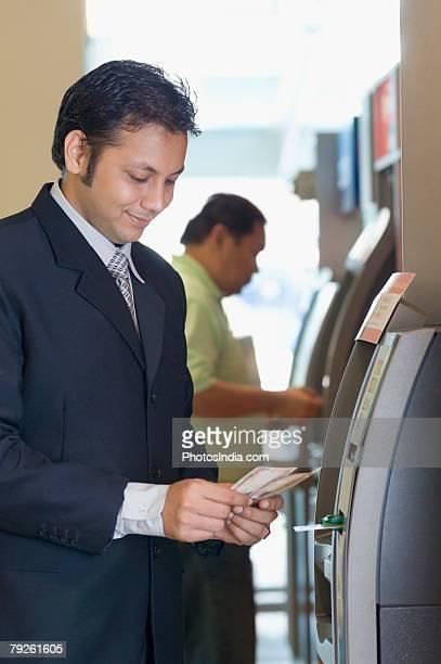 Businessman using an ATM at an airport