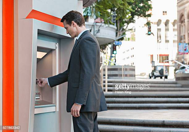 Businessman using ATM