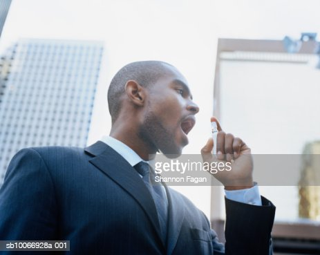 Businessman using breath freshener outdoors, low angle view : Stock-Foto