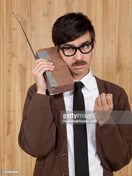 Uomo d'affari utilizzando il telefono cellulare in ufficio di mattoni