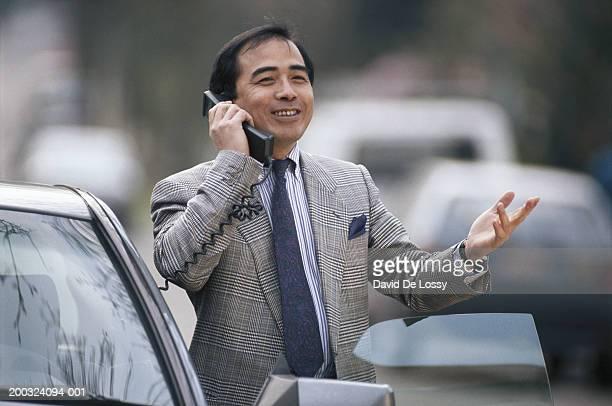 Businessman using car phone, smiling