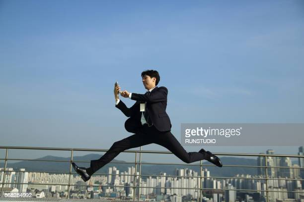 Businessman using cell phone and jumping