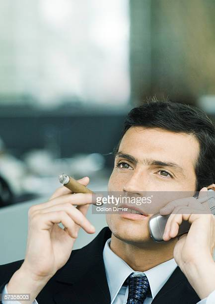 Businessman using cell phone and smoking cigar