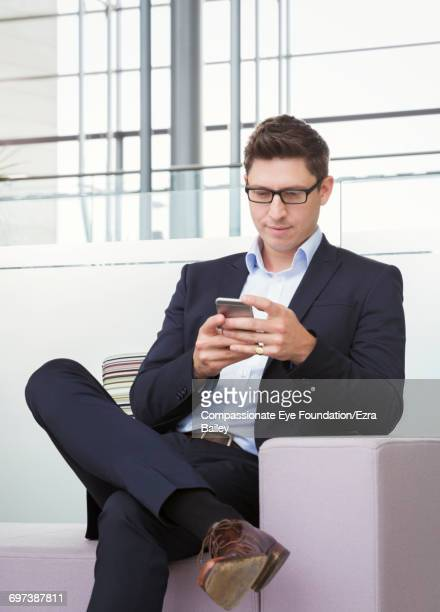 Businessman using cell phone at airport