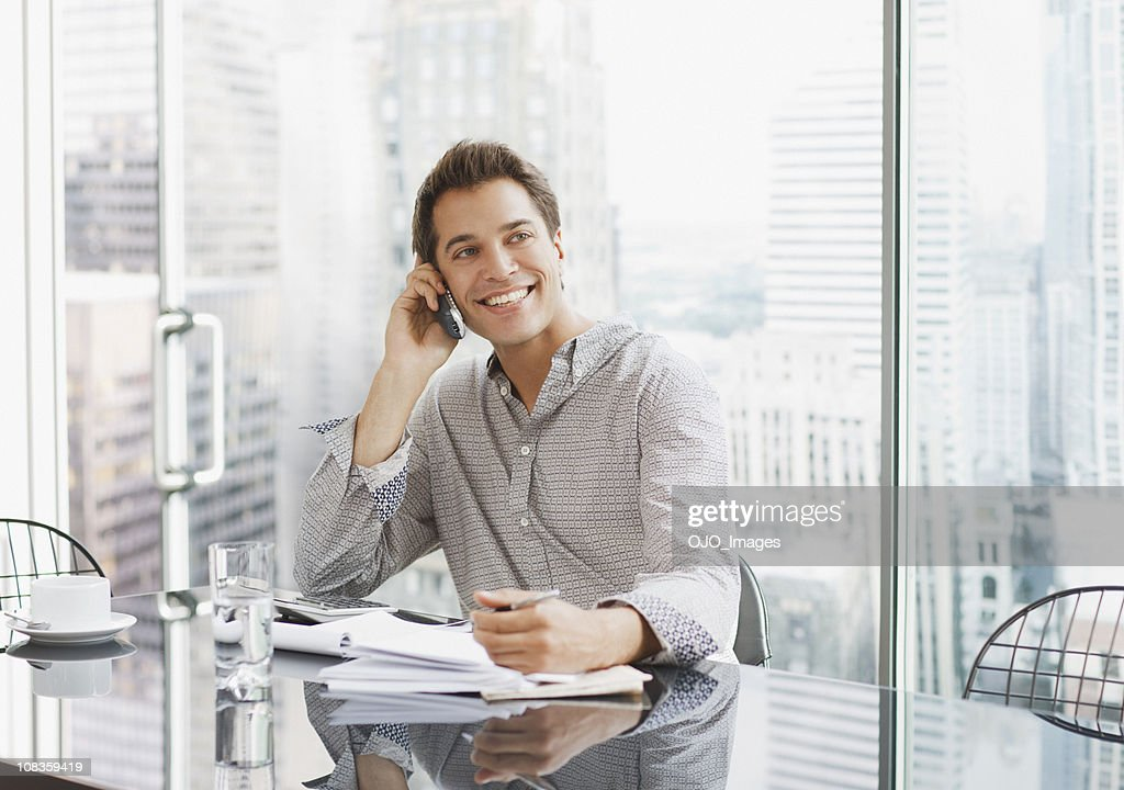 Businessman using cell phone at desk : Stock Photo