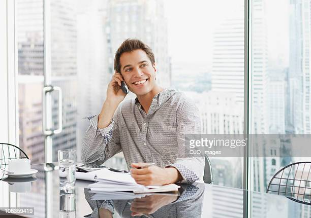 Businessman using cell phone at desk