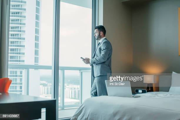 Businessman using cell phone at hotel window