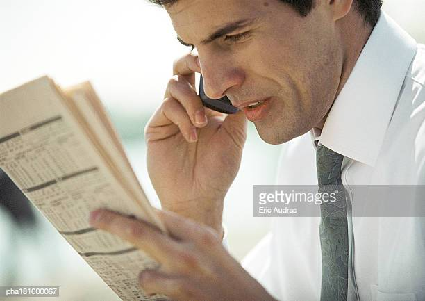 Businessman using cell phone, close-up, side view