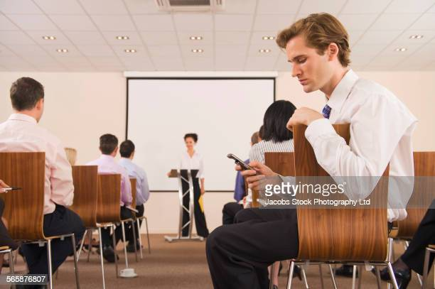 Businessman using cell phone in audience during presentation