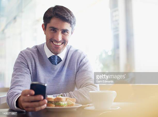 Businessman using cell phone in cafe