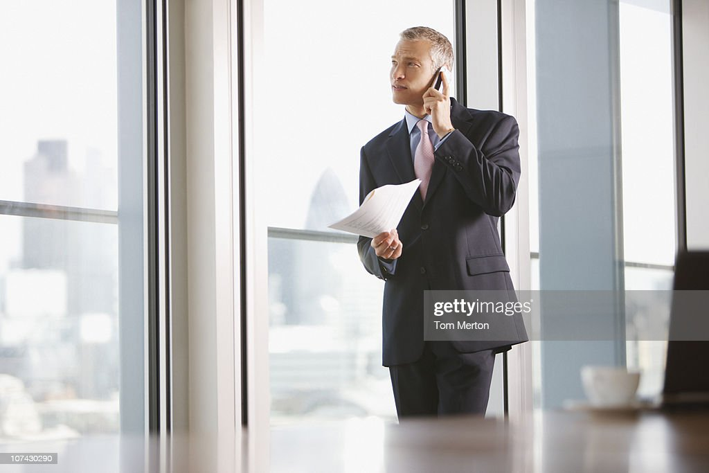 Businessman using cell phone in conference room : Stock Photo