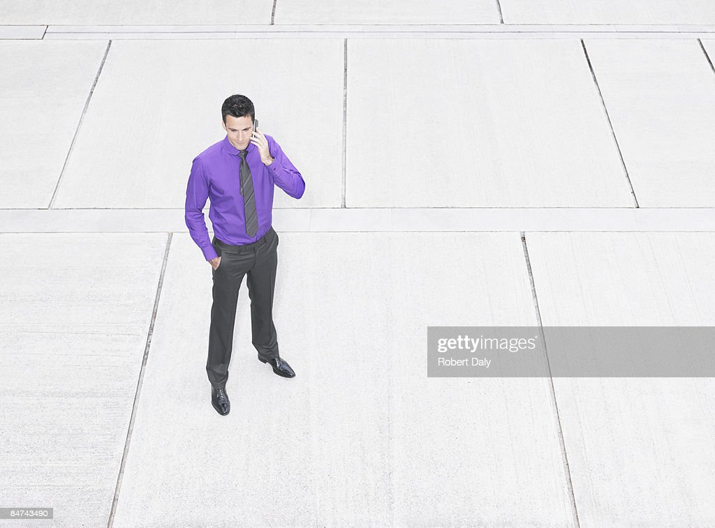 Businessman using cell phone in courtyard