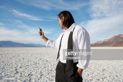 Businessman using cell phone in desert