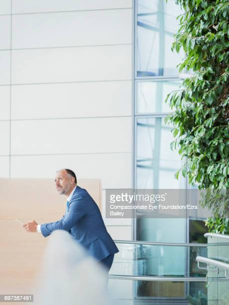 Businessman using cell phone in modern lobby