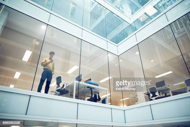 Businessman using cell phone in modern office