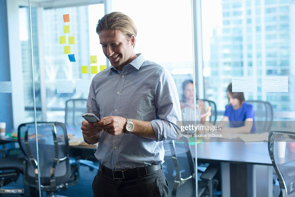 Businessman using cell phone in office : Stock Photo