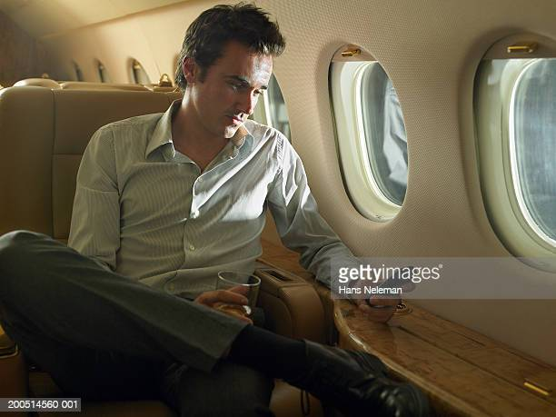 Businessman using cell phone inside private plane