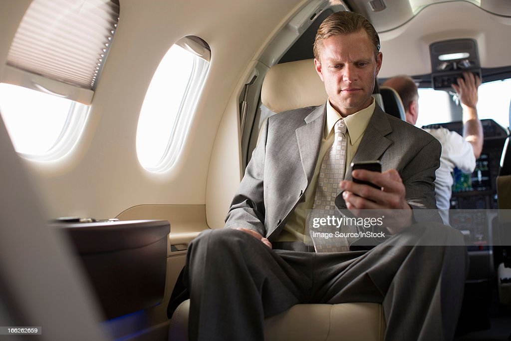 Businessman using cell phone on airplane : Stock Photo