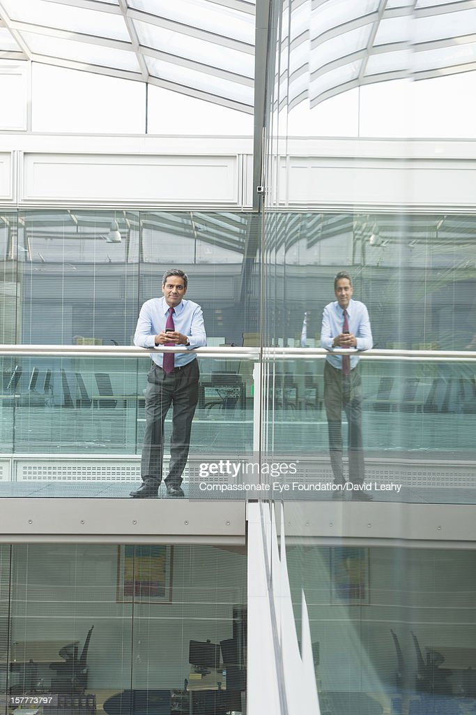 Businessman using cell phone on atrium balcony : Stock Photo