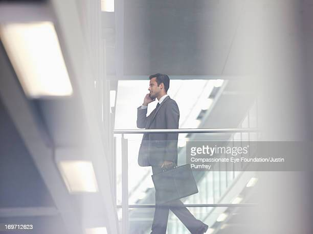 Businessman using cell phone on atrium balcony