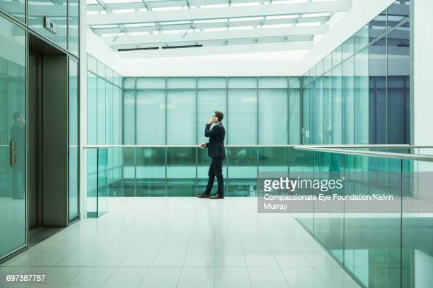 Businessman using cell phone on atrium balcony