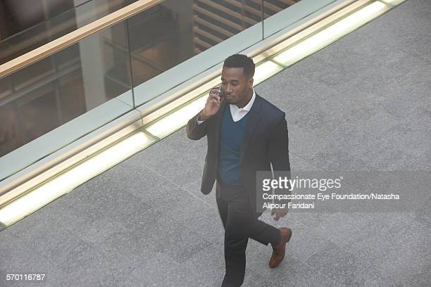 Businessman using cell phone on elevated walkway