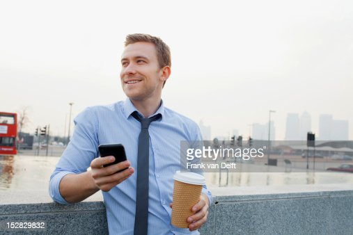 Businessman using cell phone outdoors : Stock Photo